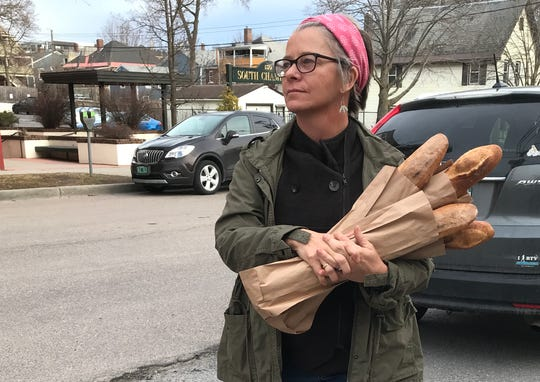 Jodi Whalen, co-owner of August First Bakery in Burlington, prepares to deliver an armful of baguettes to the Salvation Army, across Main Street, on March 18, 2020. Earlier in the day, Whalen had to lay off much of her staff due to closure of the business' restaurant and cafe.