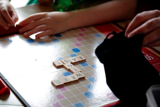 Sarah Woodward, a Cincinnati Public Schools teacher, plays a short game of Scrabble to work on spelling with her son Morgan, 8, a second grader at Seipelt Elementary, at their home  in Milford, Ohio, on Thursday, March 19, 2020. Woodward has been homeschooling her two children during the ongoing new coronavirus pandemic, but says she is concerned for fellow parents of children with special needs who can't provide all of the services their children require and get from school.