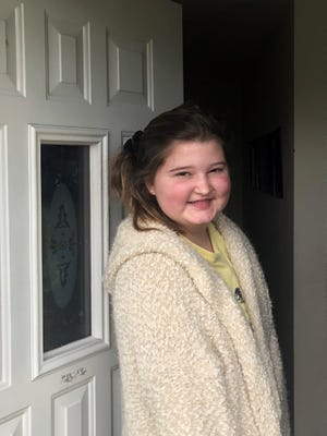 Hope Weaver, a 13-year-old heart transplant patient, stands in the door of her Mason home. Her doctors released her from a 90-day confinement in a Evanston hotel to go home to better protect her against the novel coronavirus.
