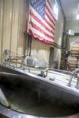 In front of a wall with a large American flag the opened top of a cauldron where corn is being cooked before fermentation to be made into 192 proof sanitizer at Old Glory Distillery in Clarksville, Tenn., on Thursday, March 19, 2020.