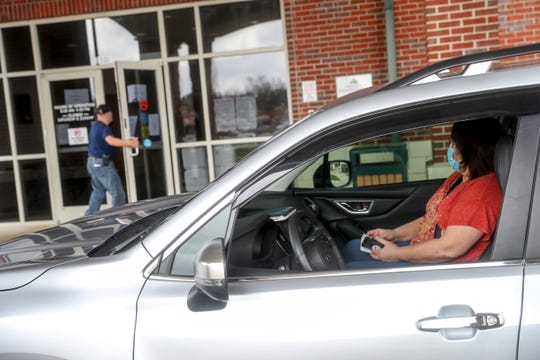 Teresa Martin, right, waits in her car as her husband Jack Martin walks in to check when medical personnel will arrive to check Teresa for COVID-19 at the Montgomery County Health Department in Clarksville, Tenn., on Thursday, March 19, 2020.