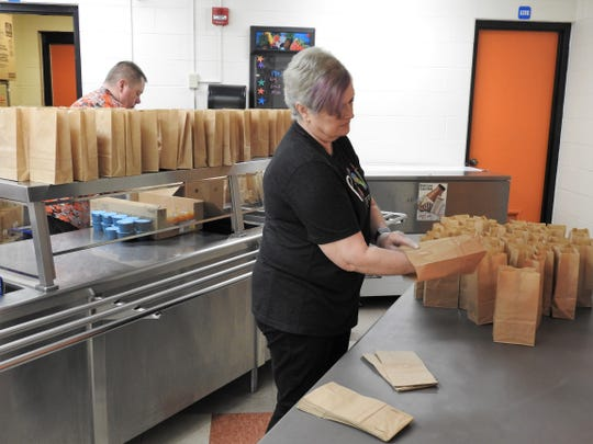 Ronda McCune readies paper bags to filled with food for the free meal program Ridgewood Schools is conducting during the COVID-19 closure. About 750 breakfasts and lunches were distributed on Thursday by pickup or delivered along bus routes.