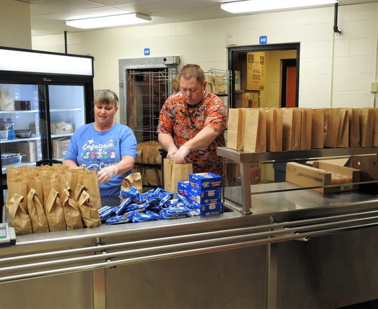 Vickie Hall and Wayne McCloy, cooks at Ridgewood Middle School, prepare lunches for the free meal program the school is offering during COVID-19 closures of schools. Students will receive a breakfast and lunch daily featuring food that doesn't need refrigerated and can keep for a time if needed.