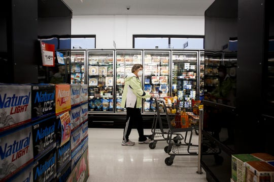 Shoppers at Fareway Grocery store pick out groceries while wearing masks during an hour designated for those more susceptible to the coronavirus on Thursday, March 19, 2020, in Des Moines.