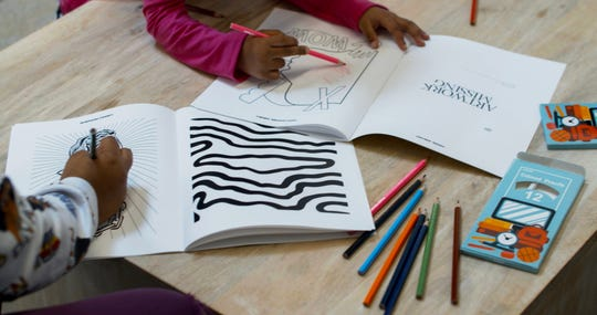Kids color inside the We All Rise sketchbook, featuring drawings from world-renowned artists.