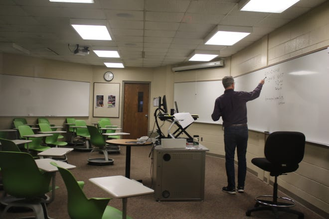 Scott Vander Linde, a professor of economics at Calvin University in Grand Rapids, teaches his class to an empty classroom with students watching online on Wednesday, March 18, 2020.