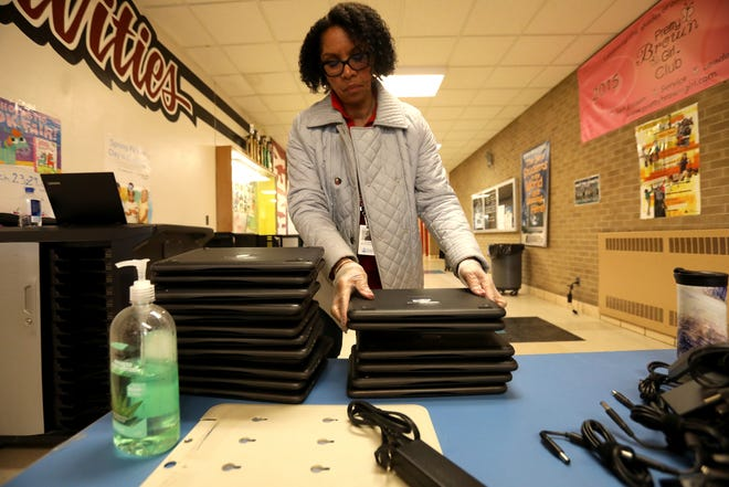 Paula Lightsey, a supervisor with Southfield Public Schools, adds more Chromebooks to a stack to be given out at Birney Middle School in Southfield, Michigan on Wednesday, March 18, 2020. The school district let parents borrow the laptops for kids to use for online learning during the COVID-19 pandemic.