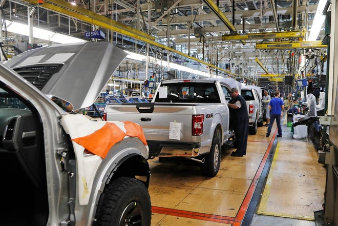 In this Sept. 27, 2018, file photo a United Auto Workers assemblymen work on a 2018 Ford F-150 trucks being assembled at the Ford Rouge assembly plant in Dearborn, Mich. Ford is suspending its dividend to preserve cash as vehicles sales fade due to the coronavirus outbreak.