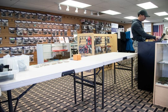 Spencer Wong, owner of Freedom Holsters Custom Kydex  in Westland, works on his computer as he waits for customers in the store, Thursday, March 19, 2020. The holster and ammunition shop has limited customers from touching their products and all CPL classes has been cancelled until further notice.