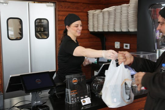 Cashier/cook Jessica Clark, 33, of Detroit, hands a customer a carryout order of wings at the Troy location of the Detroit Wing Co. on Wednesday, March 18, 2020.