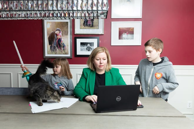 Melissa Joy, president of Pearl Planning, a wealth adviser in Dexter, is splitting working from home and the office. She's pictured with her two children at home, Josie Joy, age 6, and Gus Joy, age 10.