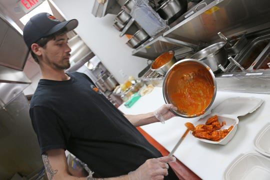 Detroit Wing Co. cook Ryan Margerison, 27, of Shelby Township, sauces an order of wings at the local chain's Troy location on Wednesday, March 18, 2020. DWC is one of the few restaurants doing well after Gov. Whitmer banned on premise dining to help combat the spread of the novel coronavirus.