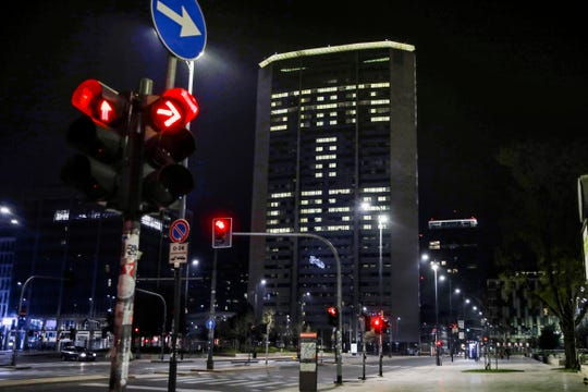 Office lights of the Lombardy region headquarters building in Milan, northern Italy, compose the Italian words 'State a casa' (Stay home), Wednesday, March 18, 2020. Italian authorities say too many people are violating last week's national decree, which allows people to leave homes to go to workplaces, buy food or other necessities or for brief strolls outside to walk dogs or get exercise.