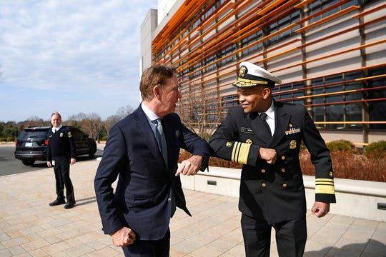 U.S. Surgeon General Vice Admiral Jerome M. Adams, right, bumps elbows with Connecticut Gov. Ned Lamont as they meet for a visit the Connecticut State Public Health Laboratory, Monday, March 2, 2020, in Rocky Hill, Conn.