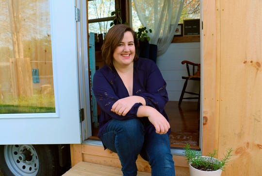 Annie Colpitts sits in a doorway of her tiny home, in Ashland, Va. Colpitts designed and helped build the home.