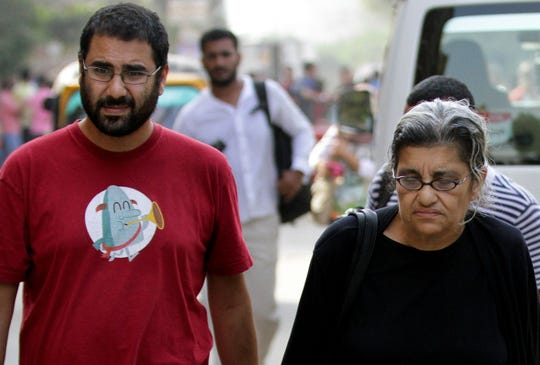 FILE - In this Oct. 26, 2014 file photo, Egypt's most prominent activist Alaa Abdel Fattah, left, walks with his mother Laila Soueif, a university professor who is an also an activist, outside a court, in Cairo, Egypt.
