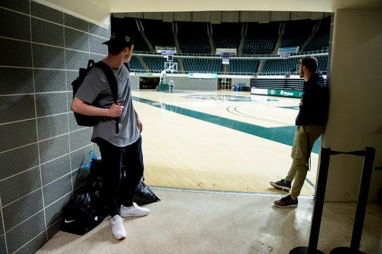 Ohio University pitchers Braxton Kelly, left, and Eamon Horwedel, stare out onto Convocation Center basketball court adjacent to their locker room after finding out the NCAA had cancelled all spring sports due to the coronavirus, on Friday, March 13, 2020, in Athens, Ohio.
