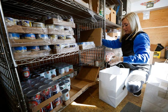 In this Tuesday, March 17, 2020, photo a volunteer loads food into a sack at the Des Moines Area Religious Council food pantry in Des Moines, Iowa.