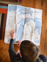 "Ben Campbell, 12 looks over a map of railways in Michigan while working on his locomotive whistle ""Passion project"" which states: Research anything you are interested in and prepare a verbal, written presentation for dinner that night.  Lisa Rajt and husband Mark Campbell home schooling their children Ben Campbell, 12 and Abby Campbell, 10 in Pleasant Ridge."