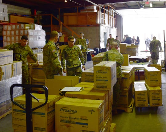 The Michigan Army National Guard gathers and loads personal protective gear, such as gloves, gowns and face shields in a mid-Michigan warehouse after being called up Wednesday (March 18, 2020) by Gov. Gretchen Whitmer.