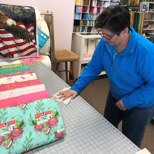Patti Mitrowski, co-owner of Sew Many Things Sewing Center, sanitizes a tabletop in her Clinton Township shop.