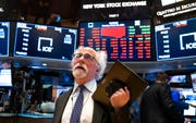 In this March 16, 2020 file photo, trader Peter Tuchman works on the floor of the New York Stock Exchange.  Wall Streetâ's plunge into a bear market after a nearly 11-year bull market has been fast and severe, erasing nearly all the S&P 500's gains since Donald Trump's inauguration. The economic disruptions from the coronavirus pandemic and a steep drop in oil prices have many economists forecasting a global recession as early as next month.