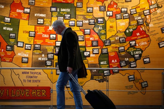 A traveler checks his mobile telephone while passing a map of the United States on the way to the security checkpoint in the main terminal in Denver International Airport in Denver on Tuesday.