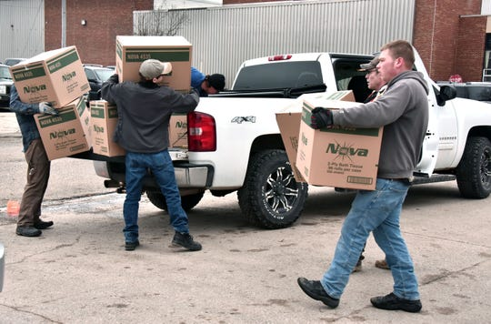 MIke Goddard, 28, right, works with others to load cases of toilet tissue on Wednesday.