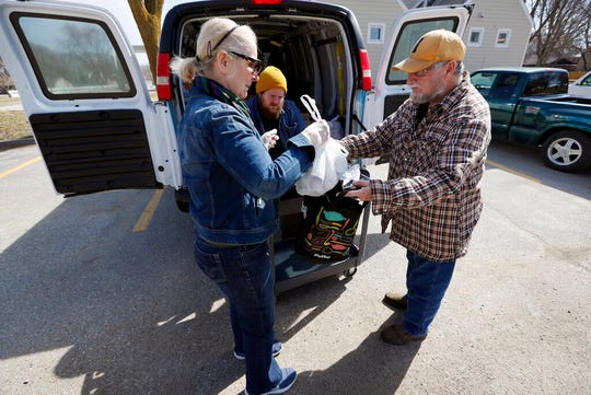 In this Tuesday, March 17, 2020, photo Des Moines Area Religious Council food pantry volunteer Louise Minor, left, hands a bag of food to Garry Vanderlinden, of Des Moines, Iowa, right, at a senior center in Des Moines, Iowa.