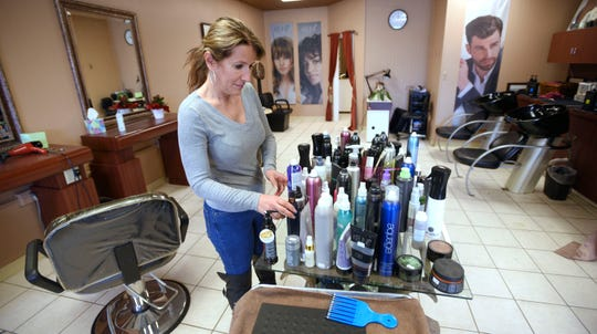 La Moda Salon owner Dee Shkreli, of Washington Twp., cleans her Shelby Twp. salon in the Nitsches Meats Delicatessen shopping center, Thursday, March 19, 2020.