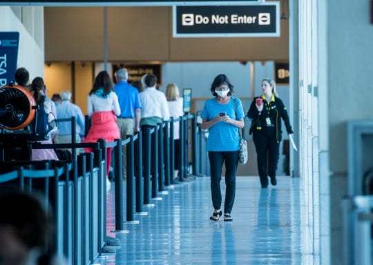 A woman heads out of one of the concourses at Southwest Florida International Airport on Thursday March 19, 2020. Traffic is down at the airport because of the coronavirus pandemic.
