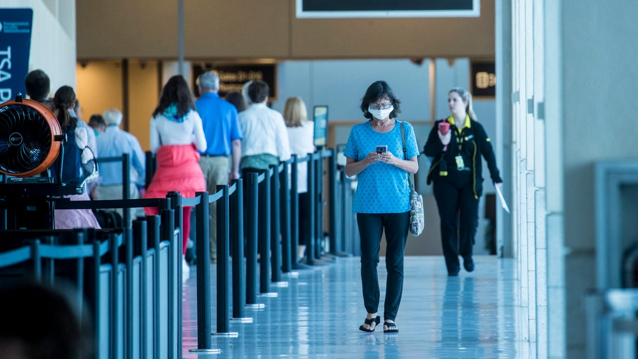 A woman heads out of one of the concourses at Southwest Florida International Airport. Travelers heading to New York, New Jersey or Connecticut will have to quarantine for 14 days upon their arrival.