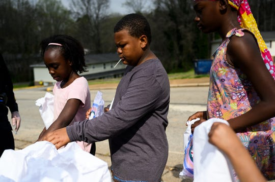 Anthony White, middle, and other children line up at a school bus meal station at Boulder Creek Apartments Thursday, March 18, 2020.