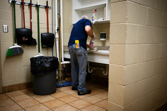 A resident at Miracle Hill Rescue Mission cleans the sinks in one of the dorm rooms at the shelter Thursday, March 19, 2020. Miracle Hill has been ramping up sanitation efforts to help prevent the spread of COVID-19 at the shelter.