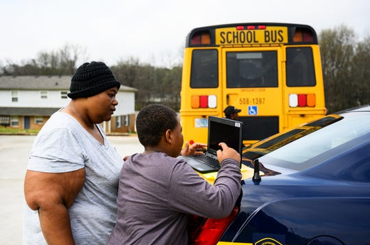 Jalisa White helps her son Anthony download his schoolwork via free WiFi available from the Greenville County School bus meal delivery program at Boulder Creek Apartments Thursday, March 18, 2020.