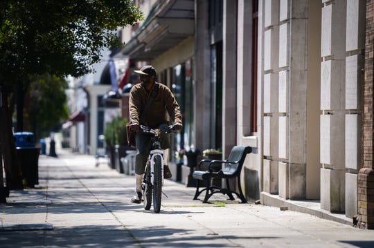 A man rides his bicycle down Broad Street in Camden, located in Kershaw County, Wednesday, March 18, 2020. The county currently has the highest number of cases of coronavirus in South Carolina.