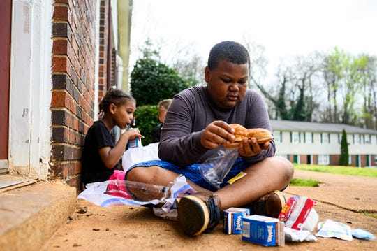 Anthony White, 9, and his younger sister Jaylah eat lunches provided by Greenville County Schools through their bus delivery service at Boulder Creek Apartments Thursday, March 18, 2020.