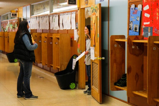 Tamara Glabraith speaks with Wendi Baune, a 2nd grade teacher at Sacajawea Elementary School, while picking up her child's remote learning packet of coursework on Wednesday, March 18.