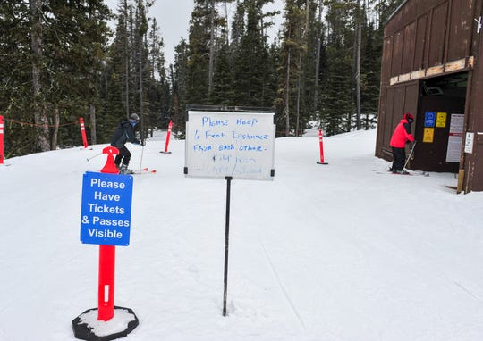 A sign at the Showdown ski lift asking people to maintain a 6 foot distance from others while waiting in line.