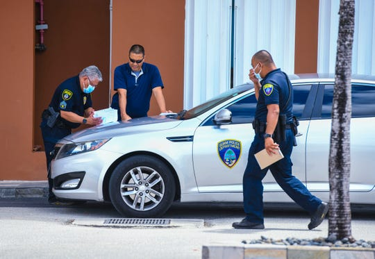 Officers with the Guam Police Department gather near the entrance of the Wyndham Garden Guam hotel on Ypao Road in Tamuning on Thursday, March 19, 2020.