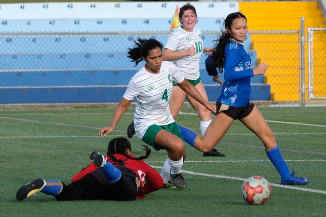 Nadine Calceta of the Triton Women's Soccer Team capitalizes on a missed grab by the Guam Women's Shipyard goalie as teammate Kaitlyn Cox stands behind ready to assist in a Jan. 12 game this year. The University suspended all sports until the Fall in an announcement made Thursday.