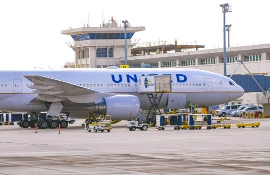 A United Airlines aircraft is serviced on the tarmac of the A.B. Won Pat International Airport in Tamuning on Thursday. March 19, 2020.