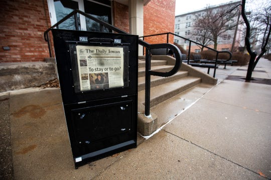 """A Daily Iowan newspaper stand displays a Friday, March 13, newspaper with the headline, """"To stay or go?"""" while University of Iowa students move out of residence hall dorms, Thursday, March 19, 2020, along Clinton Street in Iowa City, Iowa."""