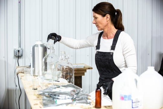 """EcoLips Director of Innovation Jen Johnson, right, measures out ingredients, Thursday, March 19, 2020, at Cedar Ridge Winery & Distillery in Swisher, Iowa. Johnson created the formula for the """"hand cleanser."""""""