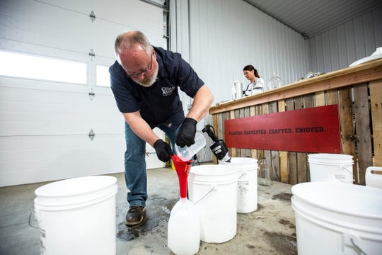 """Cedar Ridge Winery & Distillery owner Jeff Quint, center, pours """"hand cleanser"""" into a gallon container as Jen Johnson, right, measures out ingredients, Thursday, March 19, 2020, at Cedar Ridge Winery & Distillery in Swisher, Iowa. Johnson created the formula for the """"hand cleanser."""" The """"hand cleanser"""" is a 65% alcohol hand sanitizer with a lavender scent."""