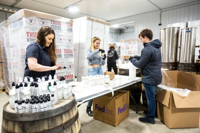 """Anna Dilyeu, left, puts labels on """"hand cleanser"""" bottles with Catherine Blades, center, and Jack Sundermann, right, Thursday, March 19, 2020, at Cedar Ridge Winery & Distillery in Swisher, Iowa. Dilyeu is the marketing manager at Cedar Ridge. The """"hand cleanser"""" is a 65% alcohol hand sanitizer with a lavender scent."""