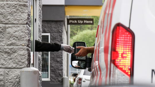 A cashier at the window of McDonald's in Meridian, Miss., takes a debit card from a customer with her gloved hand, Thursday, March 19, 2020. Most fast food restaurants are doing drive through, delivery and online order pick-ups only due to the coronavirus.
