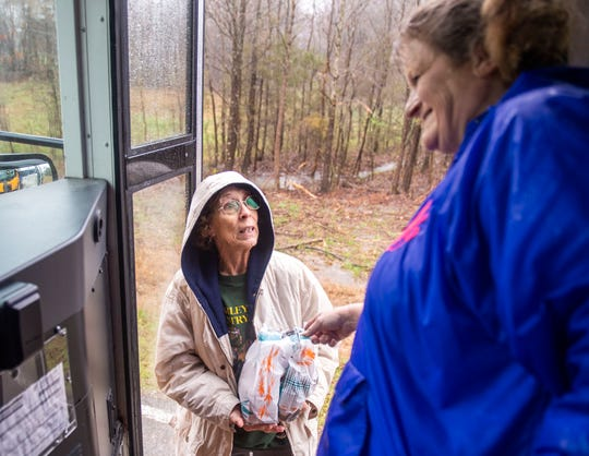 Angie Wilson talks to a student's grandmother after giving her two lunch bags for the Milan Middle school student during their spring break. This is to ensure all students have something to eat that day.