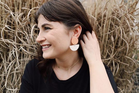 "Meg Hutchinson, AKA ""The Florista"", wearing a pair of clay earrings she made."