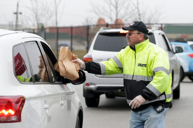Jay Jackson, a volunteer from ABATE Indiana, hands pre-bagged meals for Lafayette School Corp. students to an awaiting car at Tecumseh Junior High School, Thursday, March 19, 2020 in Lafayette.